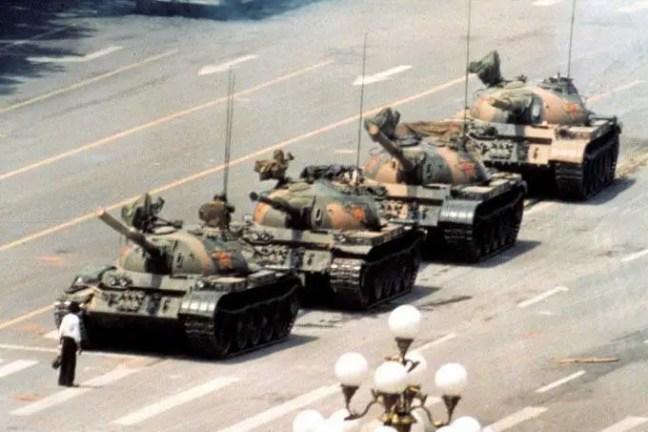 """""""O Rebelde Desconhecido"""" interrompe temporariamente o avanço de uma coluna de tanques em 5 de junho de 1989, em Pequim. Esta fotografia (uma das quatro versões semelhantes) foi tirada por Jeff Widener da Associated Press."""