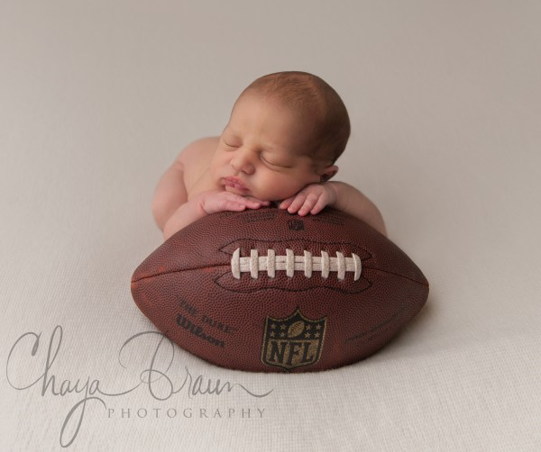 newborn baby on football