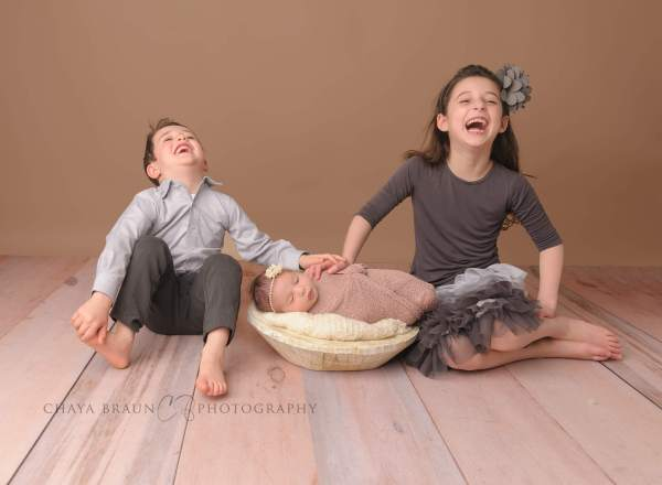 siblings and baby laughing