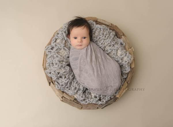 awake newborn baby boy in gray driftwood basket