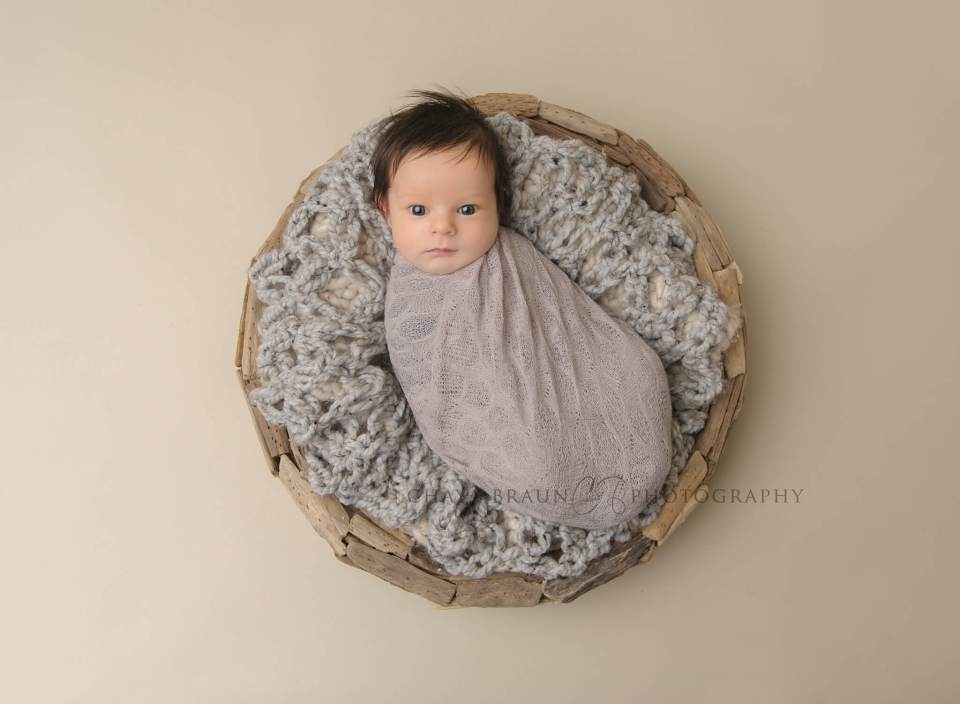 awake newborn baby boy in gray driftwood basket