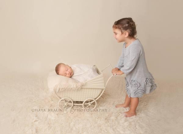 sister and newborn in pram