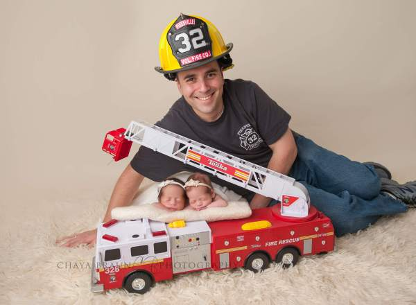 newborn twin babies with firefighter dad
