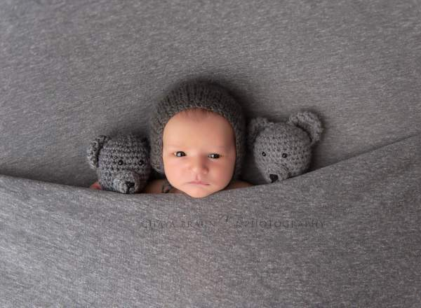 Awake newborn baby with teddy bears