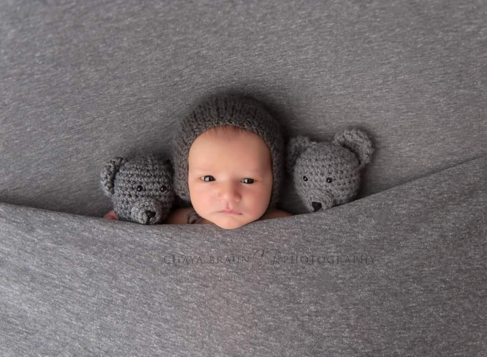 Awake newborn baby with teddy bears