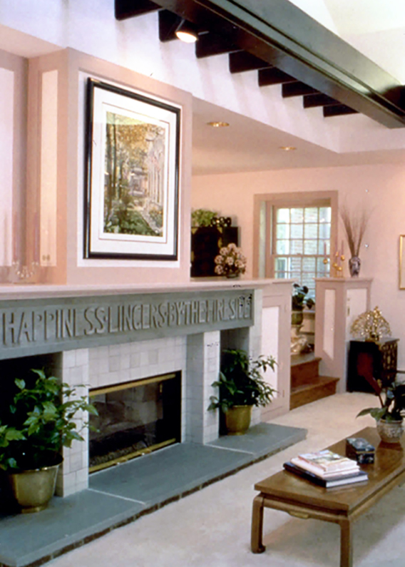 """This carriage house conversion cleverly turned original architectural elements, such as chestnut columns and a rolling barn door, into unique decorative features. But perhaps most clever was the new placement of an engraved stone lintel found buried beneath the dirt basement during renovation: """"Happiness lingers by the fireside."""""""