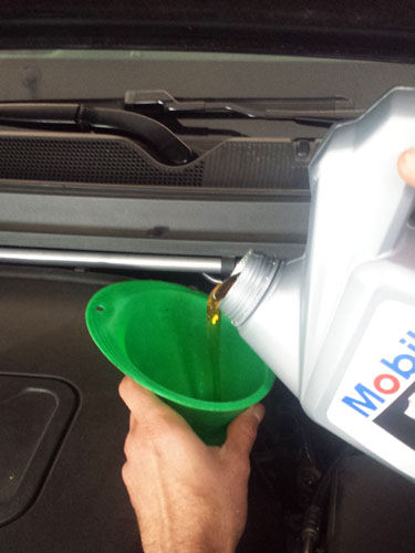 Doing an oil change, pouring new oil