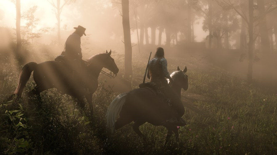 two cowboys riding horses through a forest