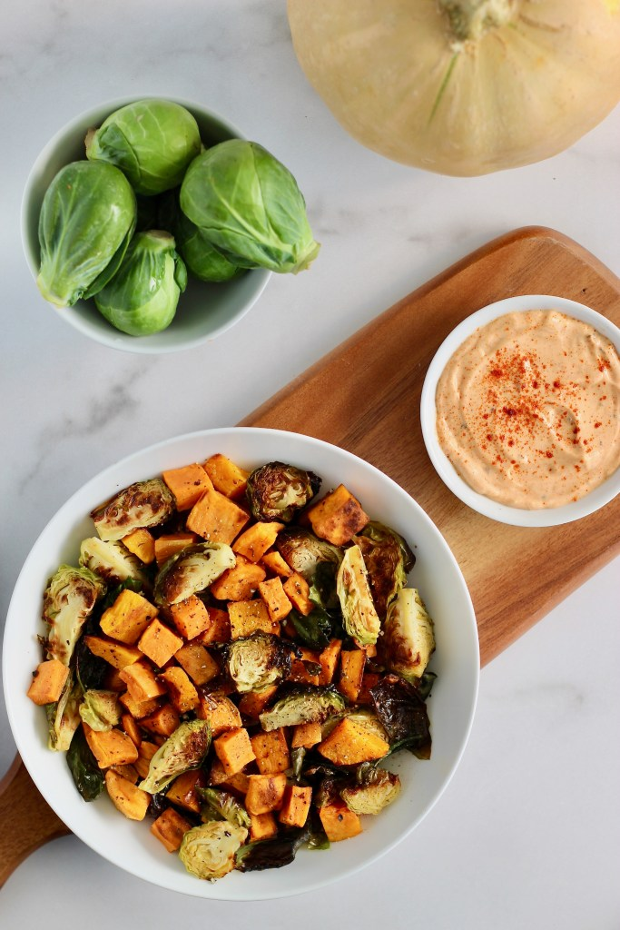 Looking for an easy side dish recipe using up all those delicious winter squash and Brussels sprouts? Try making Roasted Fall Vegetables served with Smoked Paprika Aioli sauce. It goes great alongside quinoa cakes, burgers, and salmon! #HolidaySide #Vegetarian #FallVegetables #Brussels #Squash #EasyRecipes