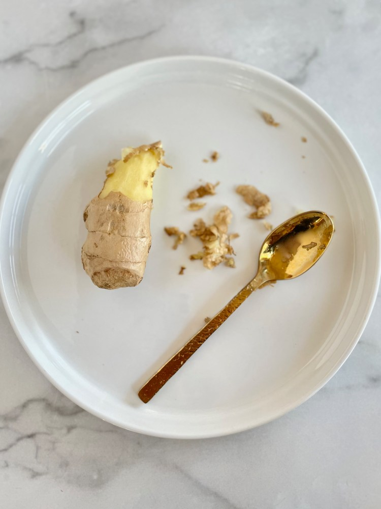 Close up of half peeled ginger and a gold spoon