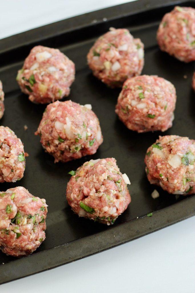 Lamb meatballs rolled on a sheet pan