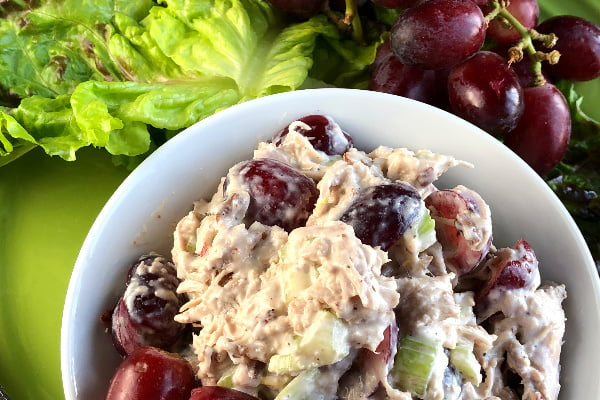 Chicken salad with red grapes and walnuts in a white bowl.