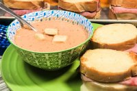 A bowl of Creamy Tomato Dill Soup with grilled cheese sandwiches.