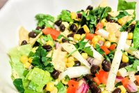 A mixed greens salad with vegetables and black beans.