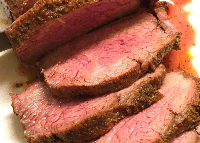 Hard to resist medium-rare sliced of beef tri tip roast.