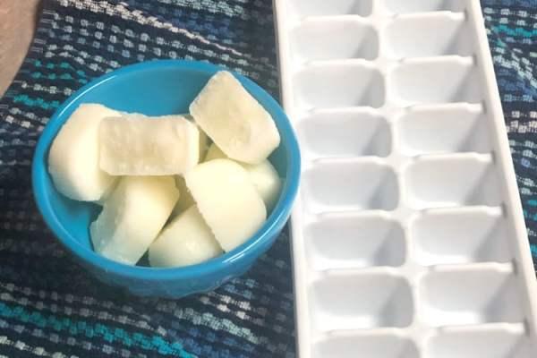 Frozen yogurt cubes in a bowl beside an ice cube tray.