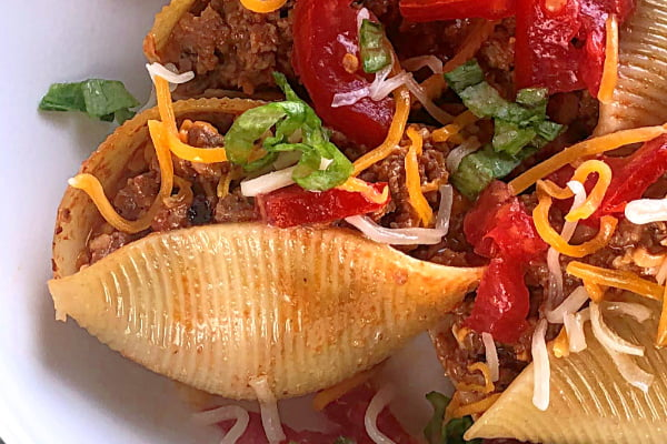 Here's a rock-solid ground beef recipe for your clan! My guys love this Cheeseburger-Stuffed Jumbo Pasta Shells casserole and I serve it up year round for them.  All the ingredients are likely already on hand in your pantry and you can throw this ground beef dish together in nothing flat. I love to make this recipe in my favorite cast iron skillet.  #speedymeal #groundbeef #casserole #skilletmeal