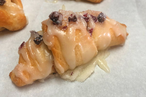 Baked crescent roll dough pastries filled with dried cranberries and toasted walnuts, topped with a powdered sugar glaze.
