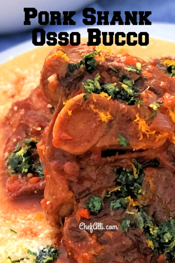 Close up shot of a pork osso bucco with gremolata garnish on a bed of polenta.