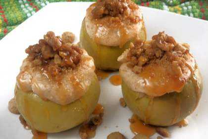 Three cheesecake-stuffed baked apples, drizzled with caramel sauce, sitting on a white plate.