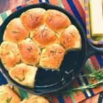A cast iron skillet full of baked dinner rolls with rosemary sprinkled over the top.