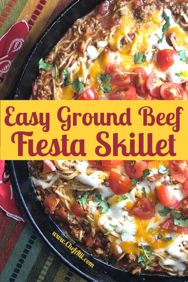 Cast iron skillet full of Fiesta Ground Beef and Noodle Skillet, topped with cheese, tomatoes, and cilantro.