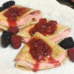 A trio of strawberry creme filled crepes with fresh berries.