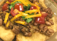 Fried Tacos with a Mexican Ground Beef Filling Topped with Tomatoes and Cheese.