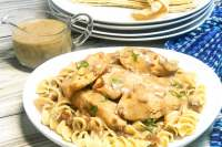 A plate full of noodles topped with chicken tender and gravy.