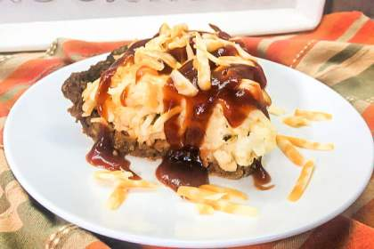 A slice of Cheesy Hash Brown Meatloaf Pie on a plate.