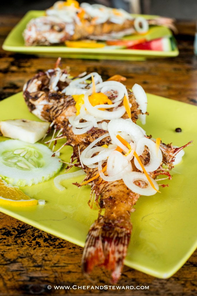 Jamaican escoveitch fish for Mother's Day brunch on green plates. Easy and tasty recipe with pickled onions on top of fried fish.