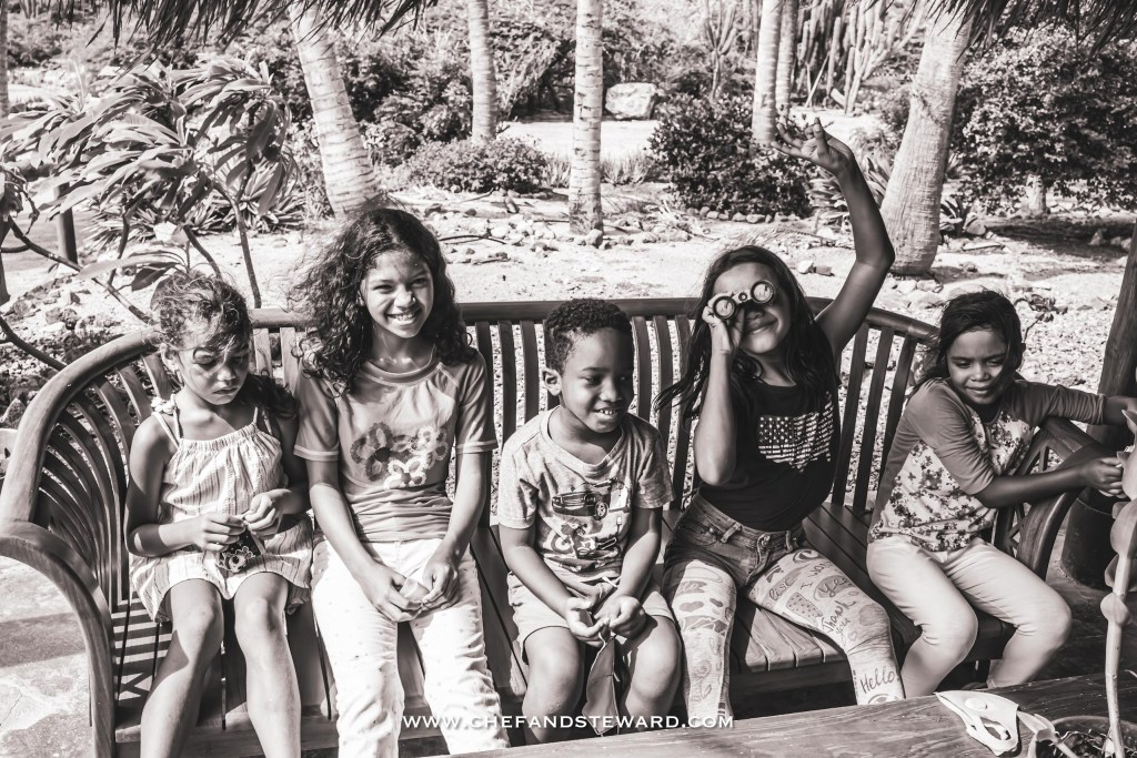 5 children sitting happily on a bench while on a tour of the Aruba Ostrich Farm right before eating at the Savanna Restaurant located there.