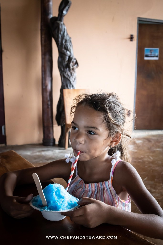 Little Girl eating blue bumble gum shaved ice at Aruba Ostrich Farm for what to do for kid activities in Aruba