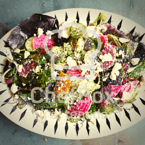 Cucumber, beets, ricotta salad in black and white plate.