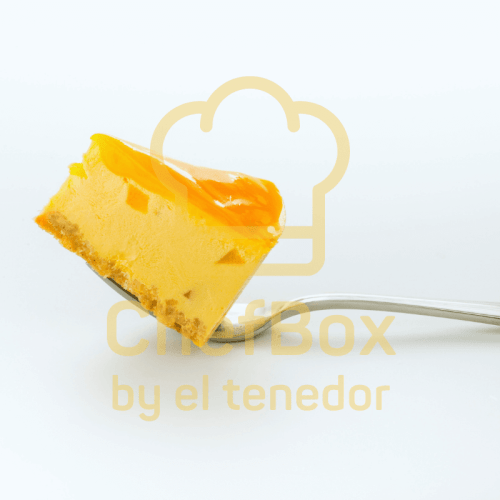 Cheesecake with mango coulis on top of a fork.