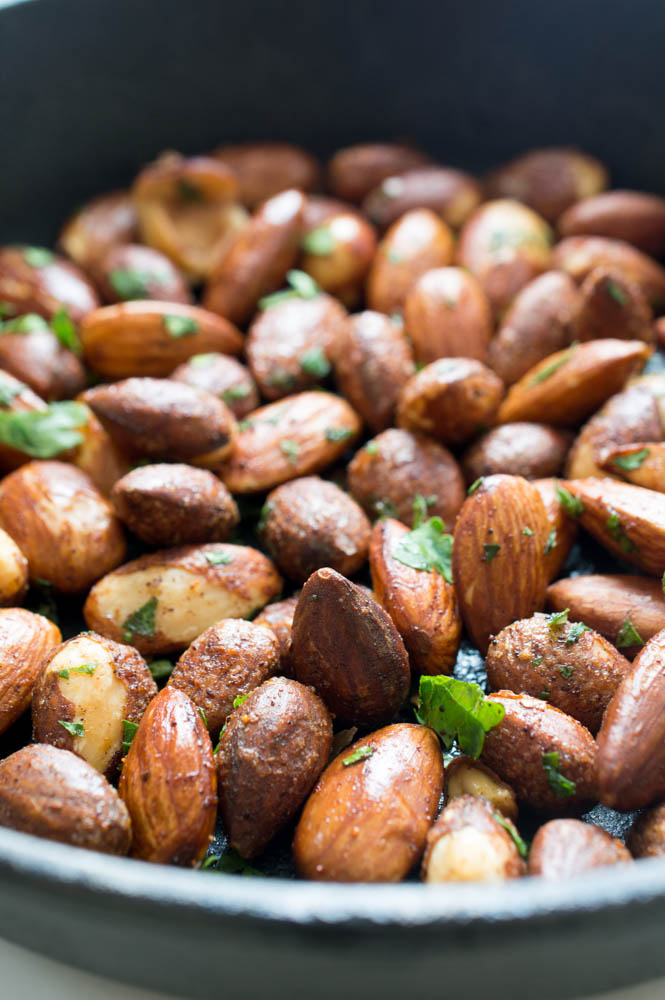 close up shot of roasted almonds in black skillet with cilantro flakes