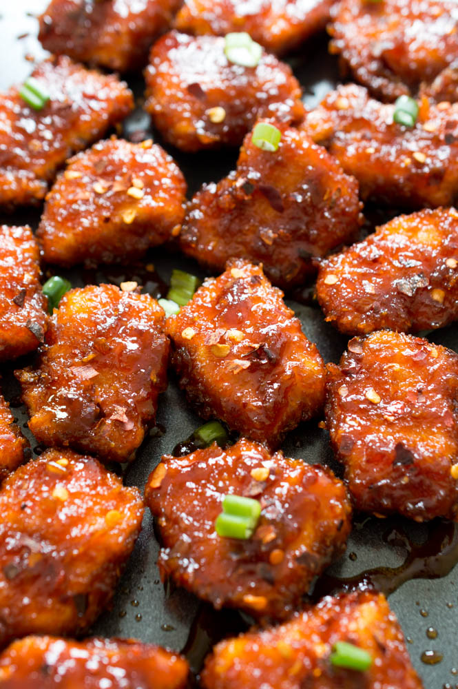 Honey sriracha chicken bites on black surface
