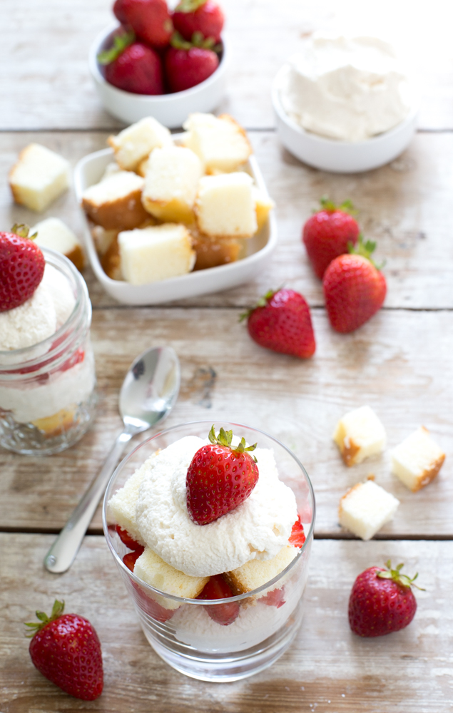 Top shot of individual strawberry shortcake trifles next to ingredients on wooden table.