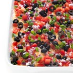 top shot of dip with olives, tomatoes, onions, beans, and sour cream in white baking dish