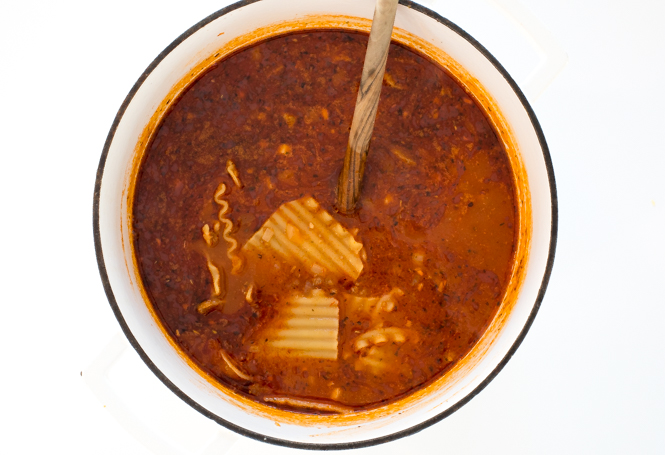 top shot of red soup in white bowl with noodles added