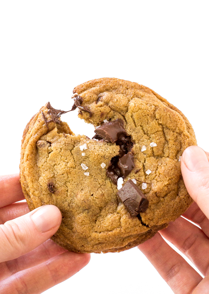 two hands pulling a gooey chocolate chunk cookie apart