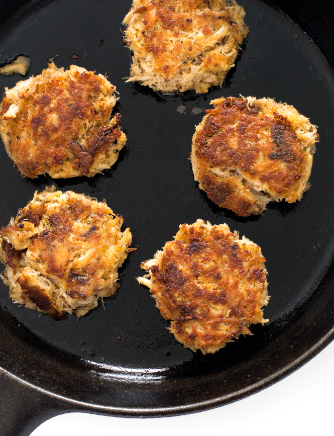 top shot of crab cakes cooking in black saucepan