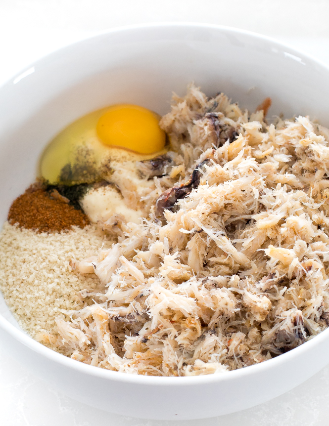top shot of shredded white meat and other ingredients in white bowl