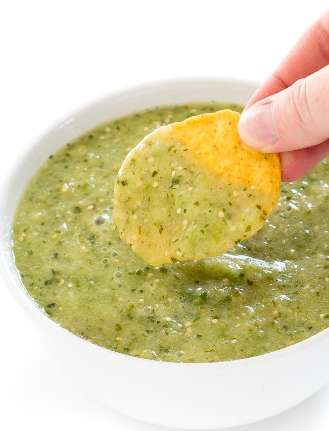 Dipping tortilla chip in tomatillo salsa