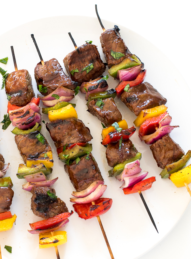 aerial view of grilled steak kabobs on white plate