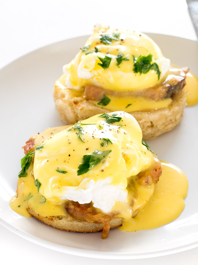 Poached eggs on english muffins and ham, topped with Hollandaise sauce, on circular white plate