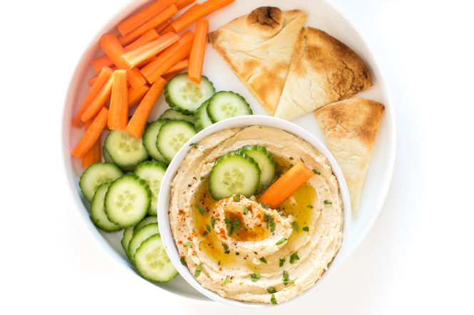 Top shot of vegetable platter with pita squares, carrots, and ground chickpeas.