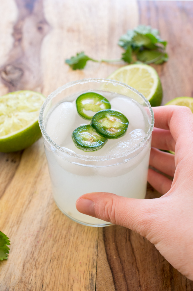 Hand holding glass filled with margarita and ice with jalapeño slices on top.