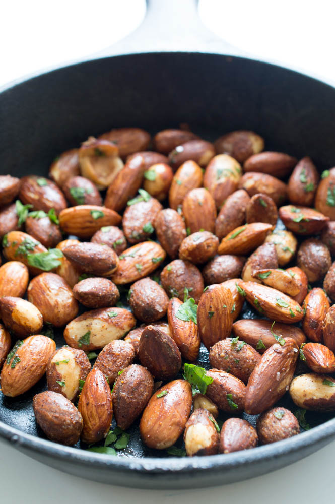 top shot of roasted nuts in black skillet with cilantro flakes