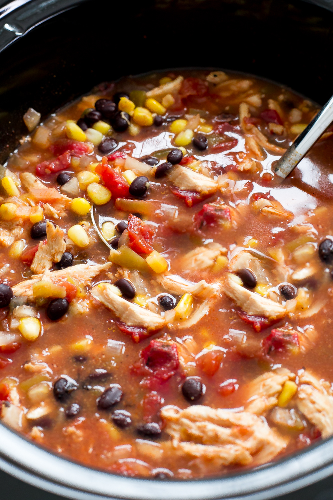 Shredded chicken enchilada soup in black slow cooker with ladle